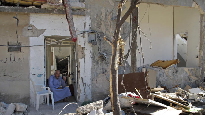 Syrian Mahmoud Jikar sits at the door of his house, which was destroyed in a Syrian government bombing last week that killed more than 40 people, in Azaz, Syria, on Monday, Aug. 20, 2012. (AP Photo/Ben Hubbard)