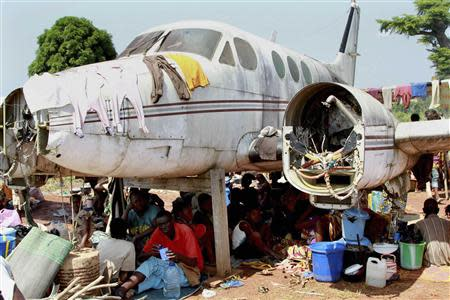 People displaced by fighting between rival militias take shelter under an old broken airplane at the airport in Bangui