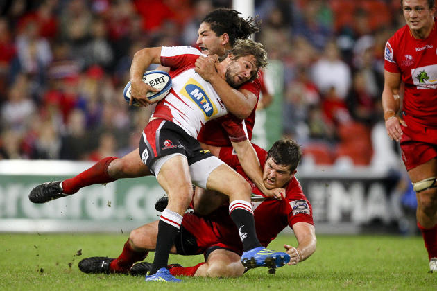 Queensland Reds player Saia Faingaa (TOP) tackles Golden Lions scrumhalf Tian Meyer (C) during their Super 15 rugby union match at Suncorp Stadium in Brisbane on May 19, 2012.  IMAGE STRICTLY RESTRICT