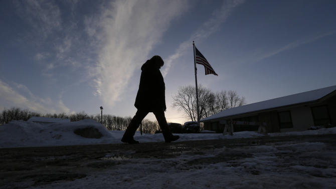 A voter heads in to the Ward 6 polling place to vote in New Hampshire's first-in-the-nation presidential primary election at sunrise in Manchester, New Hampshire