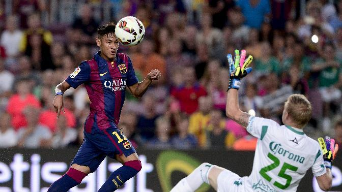 Barcelona's Neymar (L) scores against Leon's goalkeeper William Yarbrough, during their 49th Joan Gamper Trophy match, at the Camp Nou stadium in Barcelona, on August 18, 2014