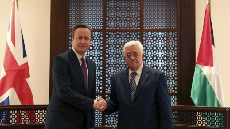 Palestinian President Mahmoud Abbas shakes hands with British PM David Cameron during their meeting in Bethlehem