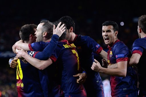 Barcelona players celebrate after Lionel Messi, from Argentina, left, scored their second goal during the Champions League round of 16 second leg soccer match between FC Barcelona and AC Milan at Camp