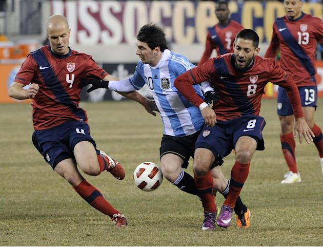 In this March 26, 2011 file photo, United States' Michael Bradley, left, and  Clint Dempsey, right, battle Argentina's Lionel Messi (10)   during the first half of a friendly soccer match at N