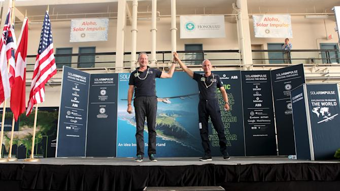 Pilot Andre Borschberg (L) and Bertrand Piccard congratulate each other at a news conference after the Solar Impulse 2 airplane, piloted by Borschberg, landed at Kalaeloa airport after flying non-stop from Nagoya, Japan in Kapolei