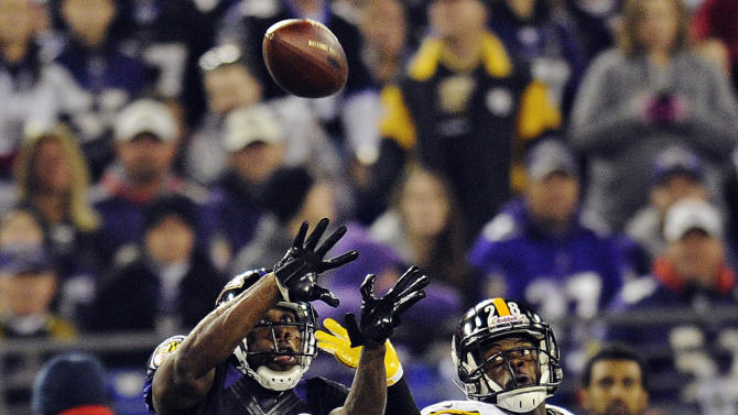 CORRECTS TO REACHES FOR A PASS NOT A TOUCHDOWN PASS - Baltimore Ravens wide receiver Anquan Boldin (81) reaches for a pass under pressure form Pittsburgh Steelers defensive back Cortez Allen, right, during the first half of an NFL football game in Baltimore, Sunday, Dec. 2, 2012. (AP Photo/Nick Wass)