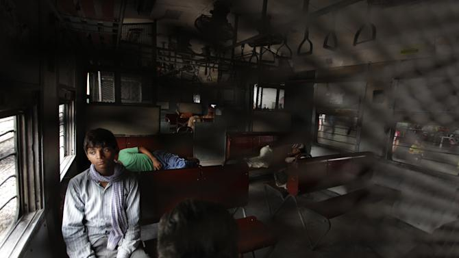 An Indian passenger sits as others sleep inside the compartment of a stationary train following the power outage that struck in the early hours of Monday, July 30, 2012 at a train station in New Delhi, India.  A major power outage has struck northern India, plunging cities into darkness and stranding hundreds of thousands of commuters. (AP Photo/Altaf Qadri)