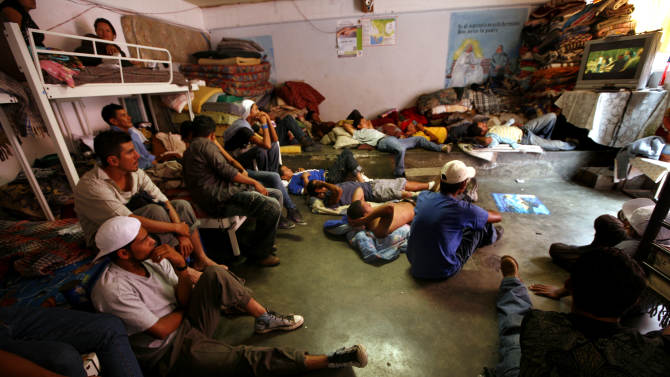 In this May 12, 2012 photo, Central American migrants watch television while waiting for a north bound train to continue their journey to the US-Mexico border, at a migrant shelter in Lecheria, on the outskirts of Mexico City. While the number of Mexicans heading to the U.S. has dropped dramatically, a surge of Central American migrants is making the 1,000-mile northbound journey this year, fueled in large part by the rising violence brought by the spread of Mexican drug cartels. (AP Photo/Marco Ugarte)