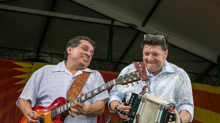 Freddie Pate on guitar, jams with Wayne Toups and the ZyDeCajun band at the Acura stage during the New Orleans Jazz and Heritage Festival in New Orleans, Friday, April 26, 2013. (AP Photo/Doug Parker)