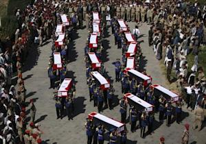 Honour guards carry coffins of soldiers and policemen killed in recent attacks during a funeral procession in Sanaa