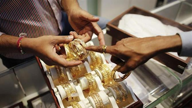 An employee shows gold bangles to a customer at a jewellery showroom on the occasion of Dhanteras, a Hindu festival associated with Lakshmi, the goddess of wealth, at a market in Mumbai November 1, 2013.