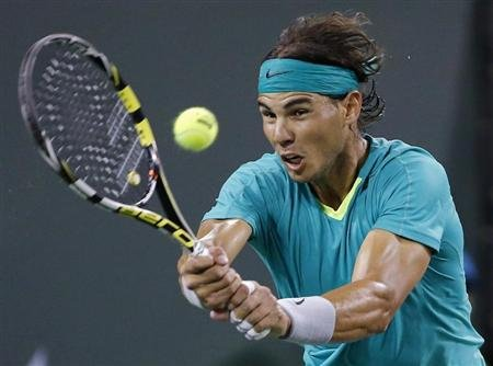 Nadal of Spain returns a shot against Federer of Switzerland during their men's singles quarterfinal match at the BNP Paribas Open ATP tennis tournament in Indian Wells