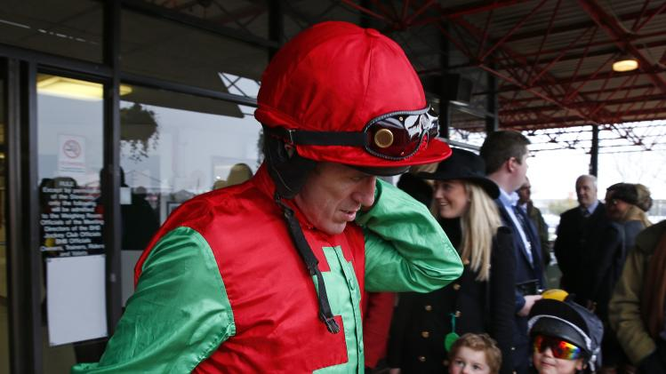 Children look up as jockey Tony McCoy leaves the weighing room before the Novices Steeple Chase at the Cheltenham Festival horse racing meet in Gloucestershire