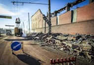 Workers repair a power line near the wall of a zinc plant damaged by a shockwave from a meteor in the Urals city of Chelyabinsk, on February 15, 2013