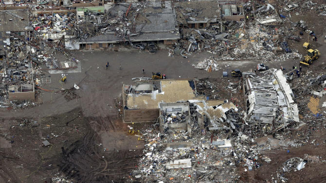 CORRECTS NAME OF SCHOOL TO PLAZA TOWERS ELEMENTARY SCHOOL - An aerial view of Plaza Towers Elementary School that was damaged in Monday's tornado Tuesday, May 21, 2013, in Moore, Oklahoma. A huge tornado roared through the Oklahoma City suburb Monday, flattening an entire neighborhoods and destroying an elementary school with a direct blow as children and teachers huddled against winds. (AP Photo/Tony Gutierrez)