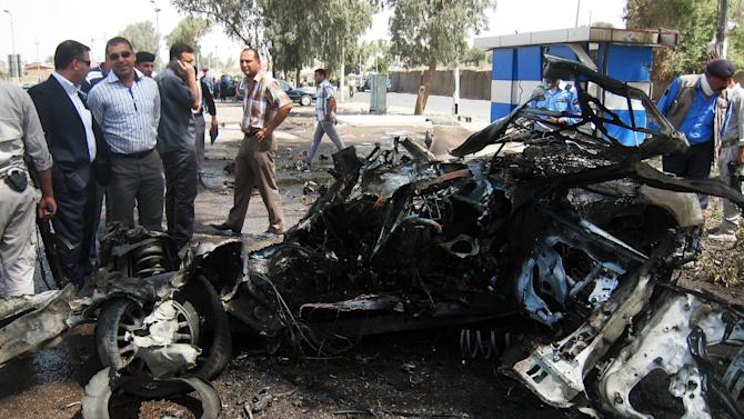 People and security forces inspect the scene of a car bomb attack in Kirkuk, 290 kilometers (180 miles) north of Baghdad, Iraq, Thursday, Aug 16, 2012.  Five separate bombings in central and northern Iraq, killed and wounded scores of people early Thursday, police said. (AP Photo/Emad Matti)