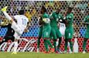 Greece's Karagounis takes a free kick which is blocked by Ivory Coast's national soccer players during their 2014 World Cup Group C soccer match at the Castelao arena in Fortaleza