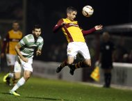 Celtic's Joe Ledley looks on as Motherwell's Keith Lasley jumps for the ball during their Scottish Premier League soccer match at Fir Park Stadium in Motherwell, Scotland December 6, 2013. REUTERS/Russell Cheyne (BRITAIN - Tags: SPORT SOCCER TPX IMAGES OF THE DAY)