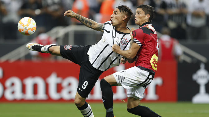 Paolo Guerrero of Brazil's Corinthians, left, is challenged by Federico Ricca of Uruguay's Danubio, as he scores his team third goal during a Copa Libertadores soccer match in Sao Paulo, Brazil, Wednesday, April 1, 2015. (AP Photo/Andre Pener)
