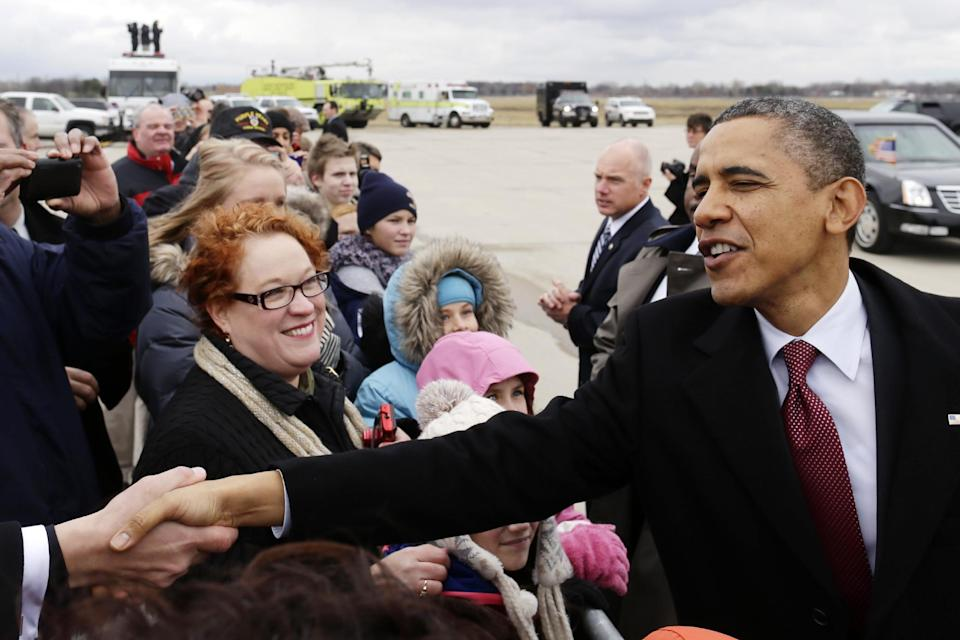 President Barack Obama greets well-wishers after stepping off Air Force One upon his arrival at  Metropolitan Wayne County Airport in Detroit, Monday, Dec. 10, 2012, before going to the Daimler Detroit Diesel plant in Redford, Mich. (AP Photo/Charles Dharapak)