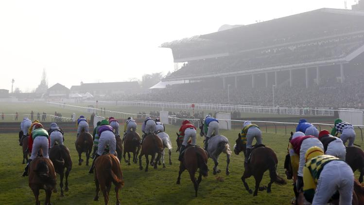 Riders and horses pass approach a fence during the Challenge Cup Handicap Steeple Chase at the Cheltenham Festival horse racing meet in Gloucestershire
