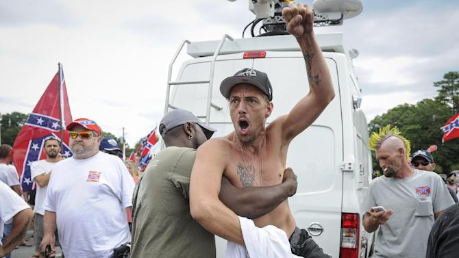 Confederate flag supporter Jerry Gray of Conyers, Ga., is held back by a fellow supporter as he yells at Ku Klux Klan members to go home, while he and others protest what they believe is an attack on their Southern heritage during a rally at Stone Mountain Park in Stone Mountain, Ga., on Saturday, Aug. 1, 2015. (John Amis/Atlanta Journal-Constitution via AP) MARIETTA DAILY OUT; GWINNETT DAILY POST OUT; LOCAL TELEVISION OUT; WXIA-TV OUT; WGCL-TV OUT