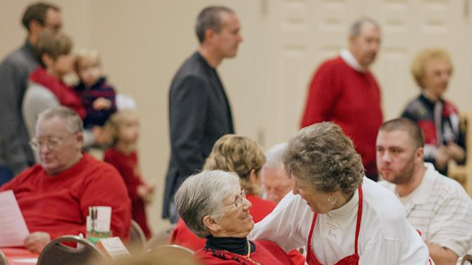 Ann Riley, right, greets Faye Babb, smiles during the First Baptist Church of Benton Annual Christmas Day Dinner in Paducah, Ky., Thursday, Dec. 25, 2014. (AP Photo/The Paducah Sun, John Paul Henry)