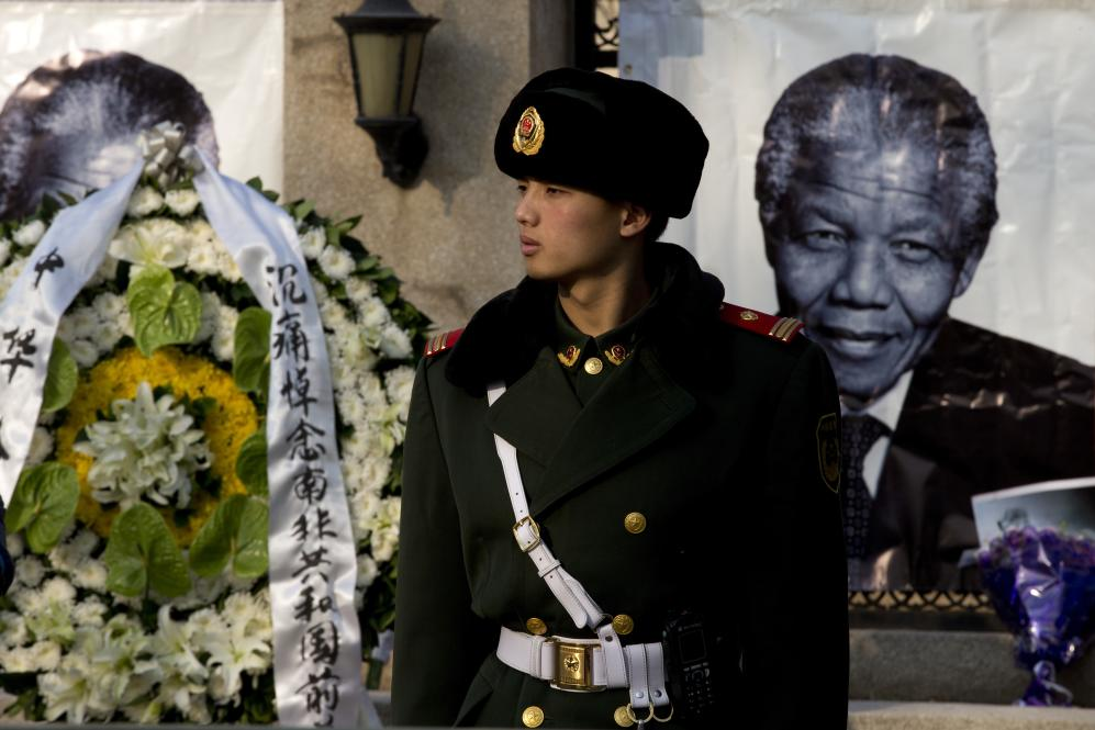 A Chinese paramilitary policeman stands guard near a wreath of flowers and a portrait of former South African President Nelson Mandela displayed outside the South African Embassy in Beijing, Friday, Dec. 6, 2013. South Africa's President Jacob Zuma said Mandela has died at age 95. (AP Photo/Andy Wong)