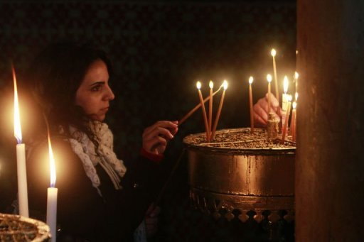 <p>A woman lights a candle at the Church of the Nativity, in the West Bank biblical town of Bethlehem, the traditional birthplace of Jesus as preparations for Christmas celebrations get underway on December 21, 2012.</p>