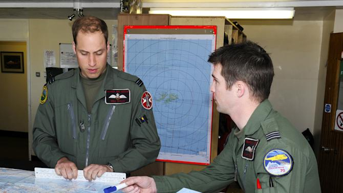 FILE - In this Feb. 4, 2012 file photo released by Britain's Ministry of Defense, Prince William, left, prepares for his first sortie with a crew member at Mount Pleasant Complex in the Falkland Islands, part of his six week deployment to the Islands. The William-and-Kate refrigerator magnets in the gift shops are about as close as most people here have come to spotting the future king of England, who has only strolled through town once so far during his tour of duty in the Falklands.  (AP Photo/Sgt. Andy Malthouse, MoD, File)