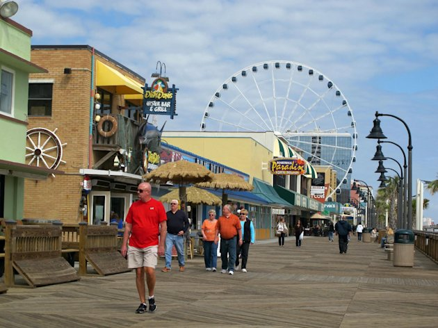 Visitors walk along the boardwalk in downtown Myrtle Beach, S.C. (AP Photo/Bruce Smith).