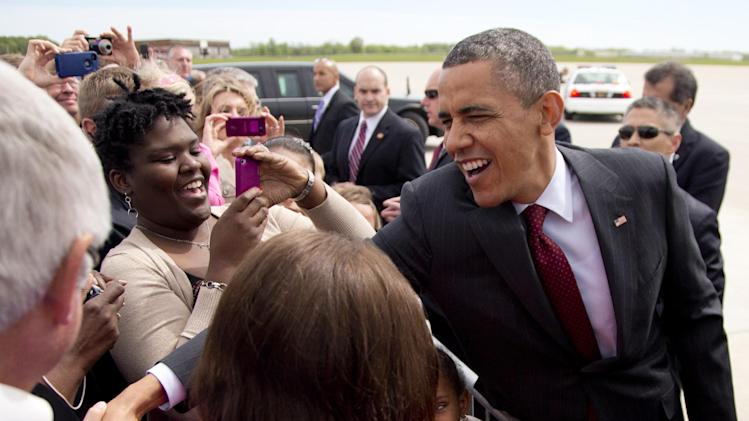 President Barack Obama greets people waiting for him on the tarmac as he arrives on Air Force One at Rickenbacker International Airport, Sunday, May 5, 2013, in Columbus, Ohio, en route to speak at the Ohio State University spring commencement. (AP Photo/Carolyn Kaster)