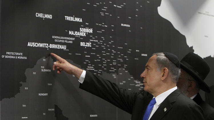 Israeli Prime Minister Benjamin Netanyahu points at a map showing where Jews were killed during the Holocaust at the opening of a new pavilion at the former Nazi death camp of Auschwitz, in Oswiecim, Poland, Thursday, June 13, 2013. The exhibition in Bloc 27 was curated by Israel's Yad Vashem Institute Chairman Avner Shalev. It is meant to educate visitors about the Holocaust and the Nazi Germany's quest to exterminate the Jewish people.The event closed Netanyahu's two-day visit to Poland that was steeped in symbolism, as it focused on the Jewish people's painful history there during World War II as well as on the strong relations between Poland and the Jewish state today. (AP Photo/Czarek Sokolowski)