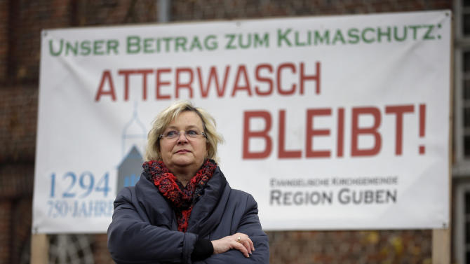 Monika Schulz-Hoepfner stands beside a protest poster against Vattenfall open-cast mining in the small village of Atterwasch, eastern Germany, Tuesday, Nov. 18, 2014 close to the Jaenschwalde lignite open-cast mine. Red slogan reads 'Atterwasch stays!'. Lignite, as this form of compressed peat is known, is becoming an increasingly important part of Germany's effort to phase out nuclear energy. It's also the reason why Atterwasch, a village that survived the Thirty Years' War, a Soviet onslaught during the final months of World War II and four hard decades of communist rule will soon be razed. (AP Photo/Michael Sohn)