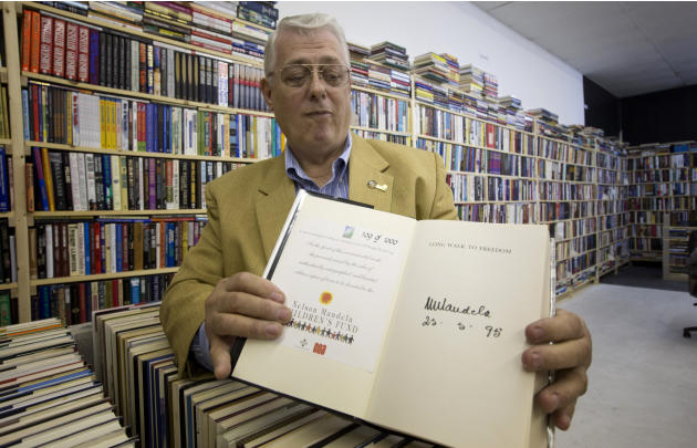 In this Friday, Oct. 19, 2012 photo, memorabilia collector Ken Kallin poses with a copy of his autographed Nelson Mandela book from his collection in Oakland Park, Fla. Three decades ago, Kallin began