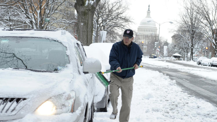 Gary Staples of Washington, clears of snow off of his car near Capitol Hill in Washington, Monday, March 17, 2014. Snow has been falling in parts of the Mid-Atlantic and Northeast as winter-weary motorists faced another potentially treacherous commute Monday morning, just days before the start of spring. (AP Photo/Susan Walsh)