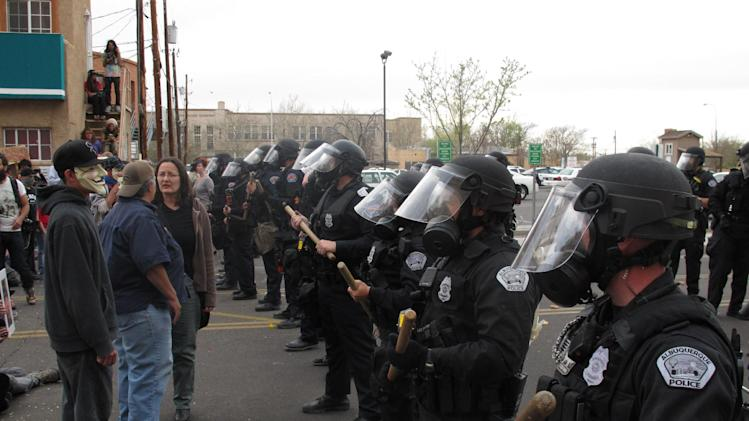 Albuquerque police face off with protesters Sunday, March 30, 2014, in downtown Albuquerque, N.M. during a protest against recent police shootings. Hundreds of protesters marched past riot police in Albuquerque on Sunday, days after a YouTube video emerged threatening retaliation for a recent deadly police shooting. The video, which bore the logo of the computer hacking collective Anonymous, warned of a cyberattack on city websites and called for the protest march. (AP Photo/Russell Contreras)