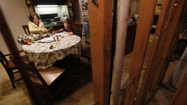 FILE - In this Thursday, Jan. 17, 2013 file photo, seen through the beams of a gutted wall, Irene Sobolov, left, sits at a table while her 10-year-old son Joey Sobolov works on his fifth grade science homework in their home in Hoboken, N.J. The living and dining rooms of the Sobolov's home, which are below ground in the basement of their home, were damaged in the floods caused by Superstorm Sandy. Three months after Sandy struck, thousands of storm victims in New York and New Jersey are stuck in limbo. Waiting for the heat to come on, for insurance money to come through, for loans to be approved. Waiting, in a broader sense, for their upended lives to get back to normal.  (AP Photo/Julio Cortez, File)