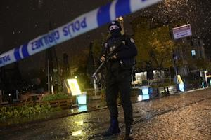 A police officer stands guard along a street after…