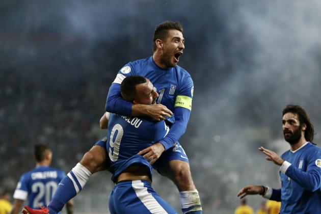 Greece's Kostas Katsouranis jumps onto Kostas Mitroglou as they celebrate Mitroglou's goal against Romania during their 2014 World Cup qualifying playoff first leg soccer match at Karaiskaki stadium i