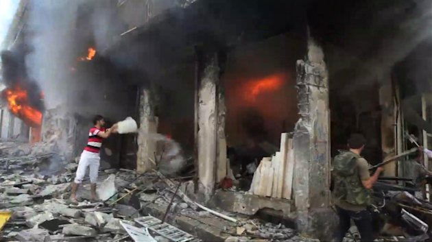This image taken from video filmed by an independent cameraman and made available on Tuesday, Sept. 4, 2012 shows a Syrian man throwing a bucket of water at a burning building in Myasar neighborhood, Aleppo, Syria. Government jets bombed the residential area of Myasar, reducing many of its buildings to rubble and causing a huge fire. (AP Photo/APTN)