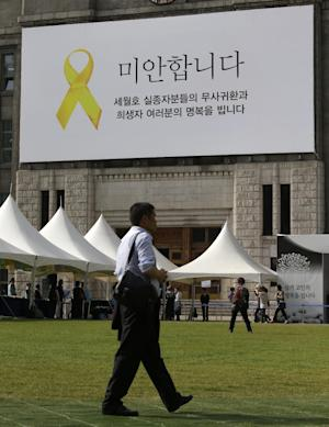 """A huge banner hanging from the front of Seoul's City Hall says """"Sorry"""" for the victims of the sunken ferry Sewol near a group memorial altar in Seoul, South Korea, Friday, May 16, 2014. One month after the ferry sinking that left more than 300 people dead or missing, there is a national debate — and spasms of shame and fury — over issues neglected as the country made its breakneck way from poverty, war and dictatorship to one of Asia's top economic, diplomatic and cultural powers. The tragedy exposed regulatory failures that appear to have allowed the ferry Sewol to set off with far more cargo than it could safely carry. (AP Photo/Lee Jin-man)"""