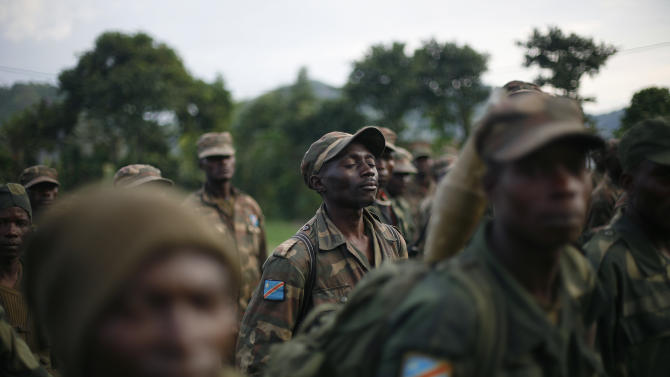 FARDC Congolese government special forces gather in a stadium  near Minova Congo, some 40 kms south-west of Goma, Thursday Nov. 29, 2012, for a moral building gathering and an address by their commander General Bahouma . M23 Rebels, who last week seized one of the most important cities in eastern Congo and advanced beyond, said Thursday that they had pulled back several miles (kilometers ) to the town of Sake and were on track to leave the key city of Goma by Friday, in accordance with a deadline imposed by the international community. Government troops were massing in Minova.(AP Photo/Jerome Delay)
