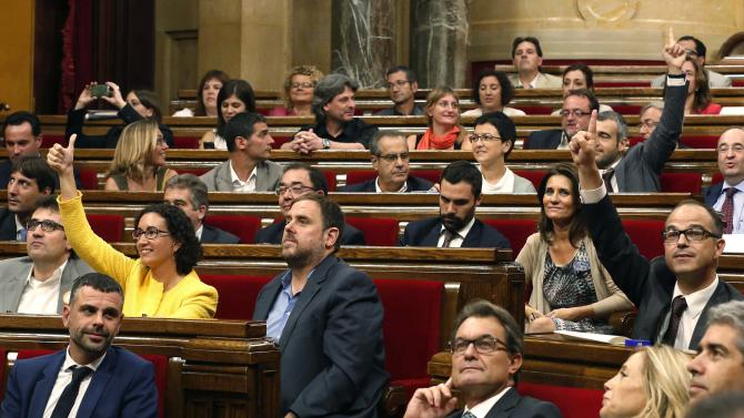 Catalonia's President Mas and ERC leader Junqueras look at the results on a screen as members of Catalonia's Parliament vote on a regional consultation law in Barcelona