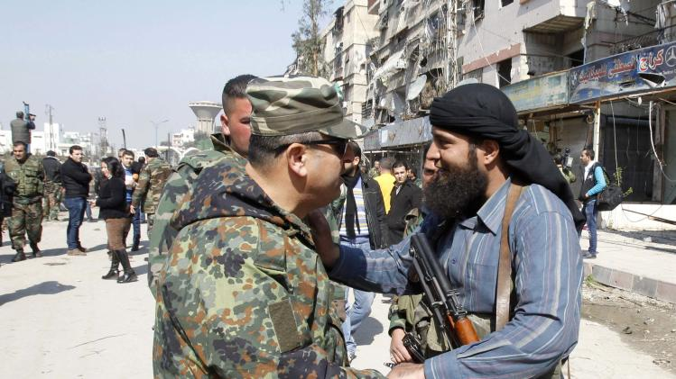 File photo of a member of Syria's armed opposition forces chating with an officer from the forces loyal to Syria's President Assad in Babila town, southeast Damascus, after a local ceasefire agreement was reached