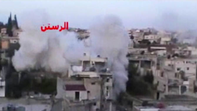In this image taken from video obtained from the Ugarit News, which has been authenticated based on its contents and other AP reporting, smoke rises from buildings after rockets slammed into them in the rebel-held town of Rastan, Syria, just north of Homs, Friday, Jan. 25, 2013. Regime troops shelled the city of Homs on Friday as soldiers battled rebels around the central province with the same name, which was a major frontline during the first year of the revolt. (AP Photo/Ugarit News via AP video)