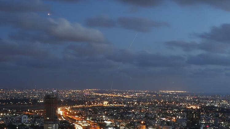 An Israeli Iron Dome interceptor rocket flies above the Tel Aviv skyline