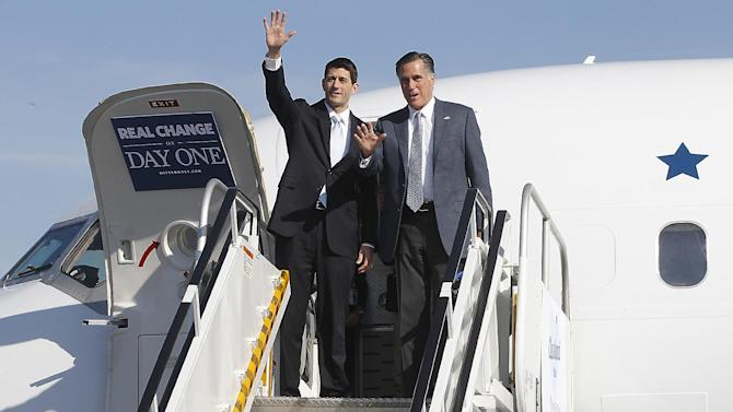 Republican presidential candidate, former Massachusetts Gov. Mitt Romney and his running mate Rep. Paul Ryan, R-Wis., wave as they exit a campaign charter airplane at Cleveland Hopkins International airport, Tuesday, Nov. 6, 2012 in Cleveland, Ohio. Ryan arrived moments earlier on his own plane and met Romney on board.  (AP Photo/Mary Altaffer)