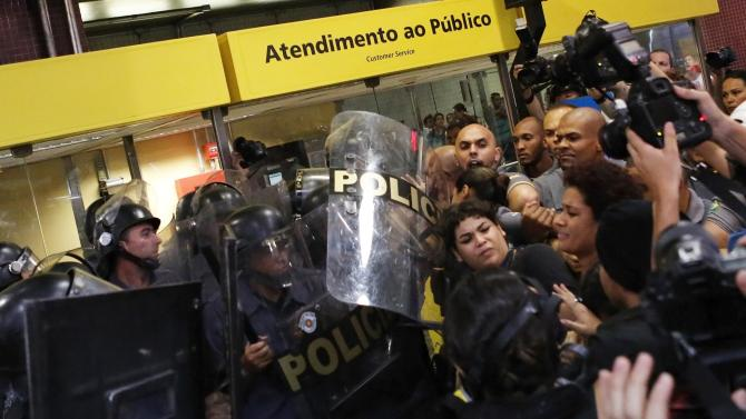 Riot police clash with demonstrators inside Faria Lima subway station during a protest against fare hikes for city buses, subway and trains in Sao Paulo