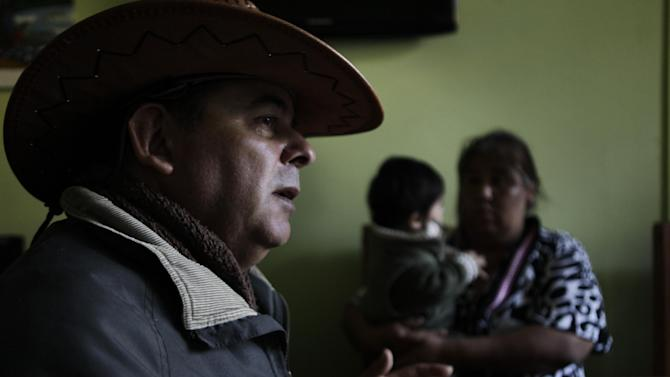 In this May 23, 2013 photo, Diaguitas leaders, Leonel Rivera Zuleta, 56, speaks during an interview as Osvaldina Guzman holds her son Tomas, in the town of Alto Del Carmen, near the facilities of Barrick Gold Corp's Pascua-Lama project in northern Chile. The Diaguitas live in the foothills of the Andes, where for as long as anyone can remember they've drunk straight from the glacier-fed river that irrigates their orchards and vineyards with clean water. But since Pascua-Lama gold mine project moved in, the Diaguitas claim the river levels have dropped and some complain of cancerous growths and aching stomachs. (AP Photo/Jorge Saenz)